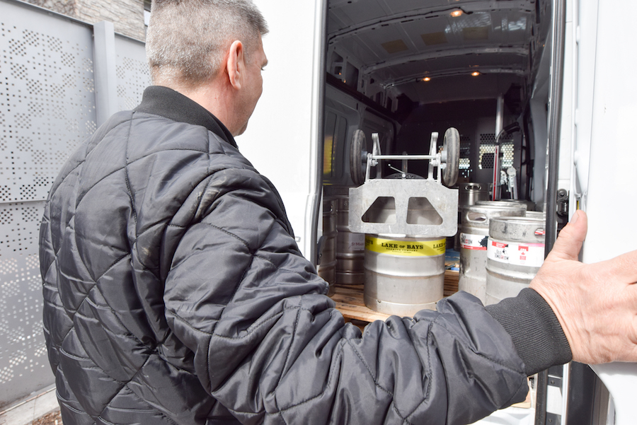 Man closing door on shipping truck full of kegs