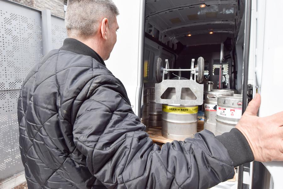 Man closing door on shipping truck full of kegs
